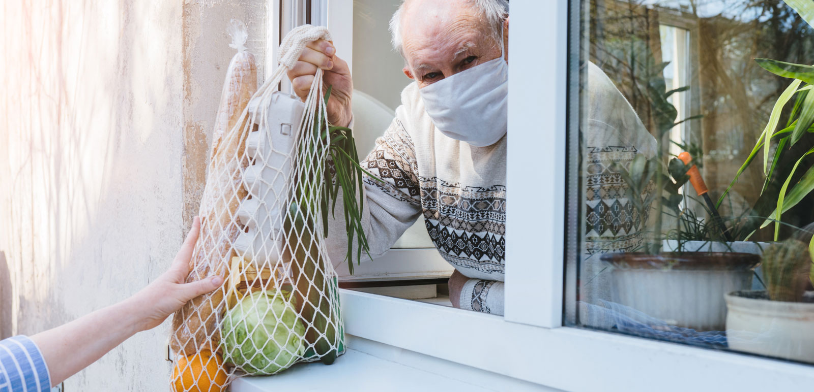Man in isolation takes groceries through window
