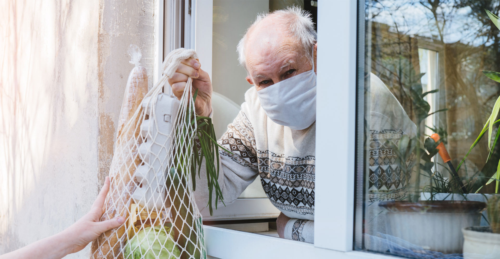 man receiving groceries through the window