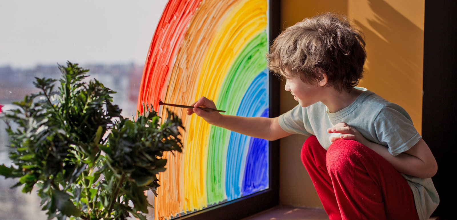 boy painting a rainbow on a window