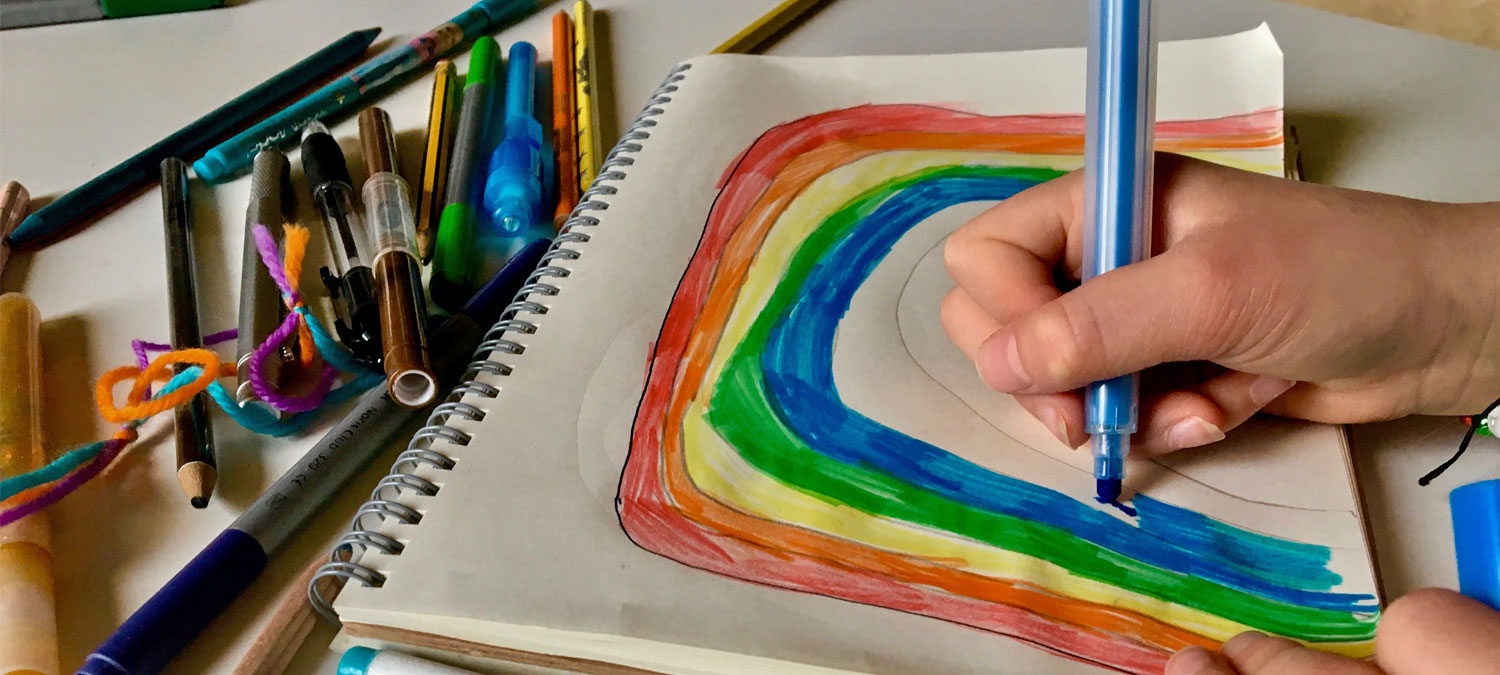 child drawing a rainbow