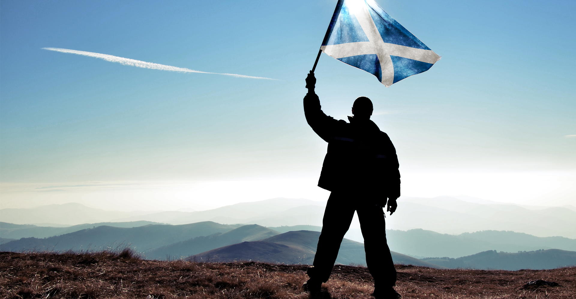 man waving a Scotland flag