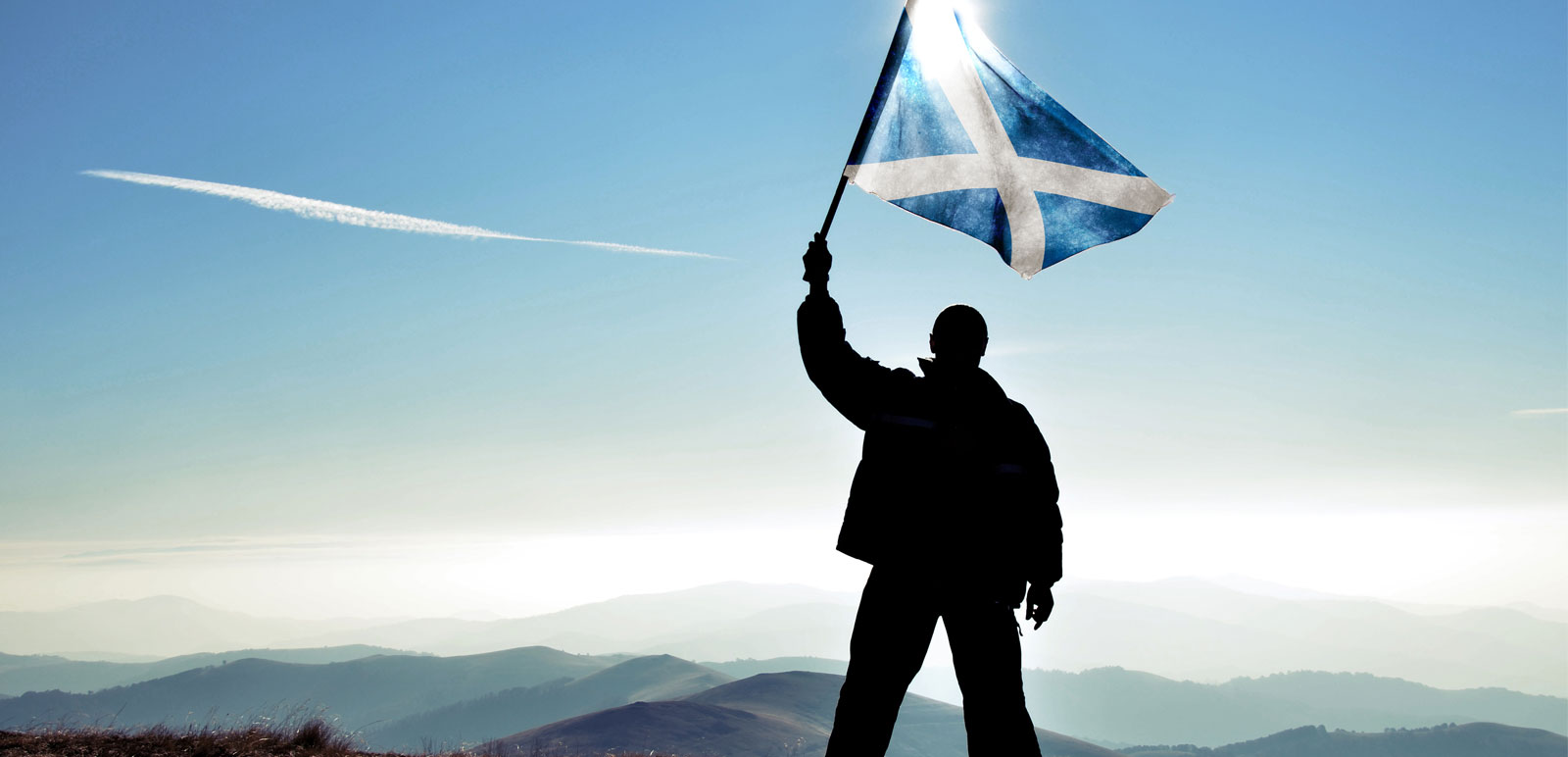 man waving a scotland flag on a mountain top